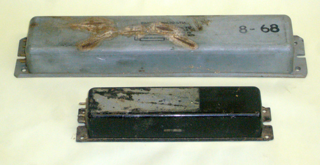 Two fluoroscent lamp ballasts that are likely to caontain PCBs. The upper one has a stamped manufacturers name of Beacon Radio.